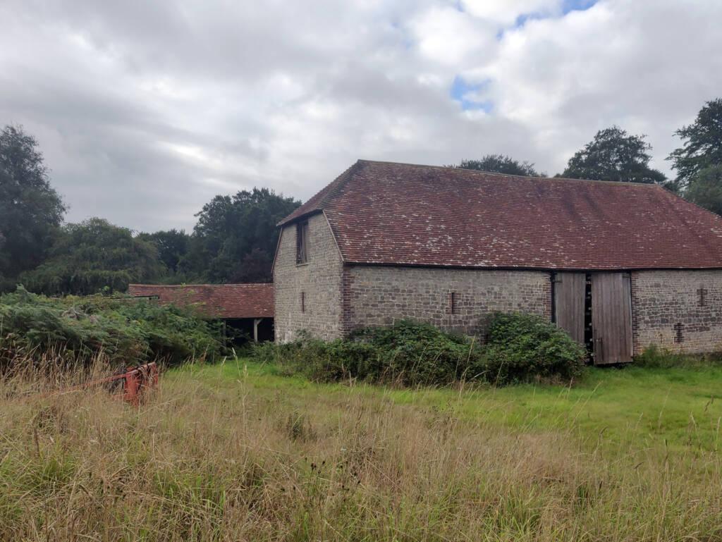A recently derelict barn with pried open door.