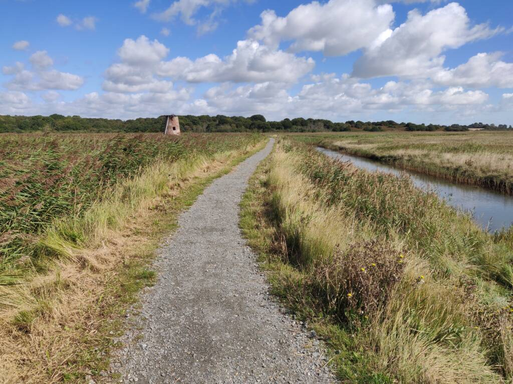 coastal trail running views over grassland and canal.